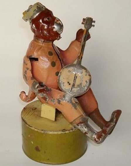 Guenthermann Tin-Figures Monkey in human clothes strums banjo, base embossed Made in