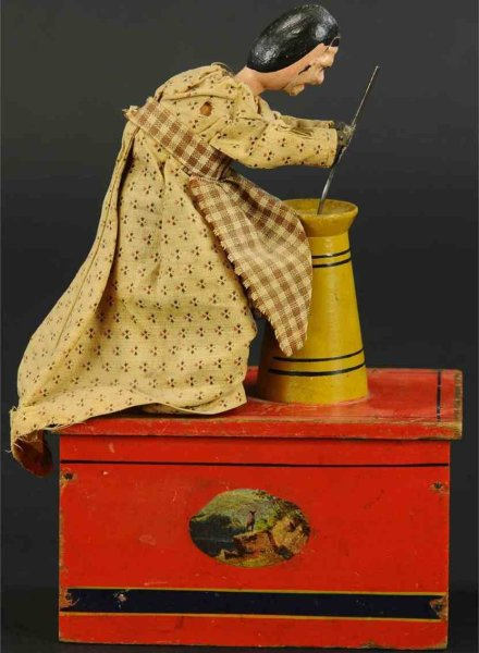 Ives Tin-Figures Butter churner clockwork toy, with wooden base and cloth-cov