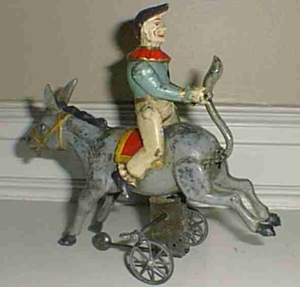 Guenthermann Tin-Clowns Clown riding a stabborn donkey, wind-up toy, when wound, the