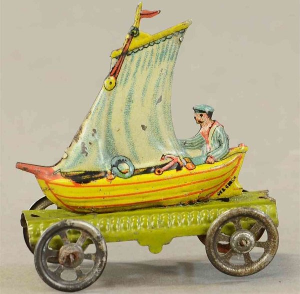 Meier Tin-Penny Toy Man in sailboat on green platform with spoked wheels