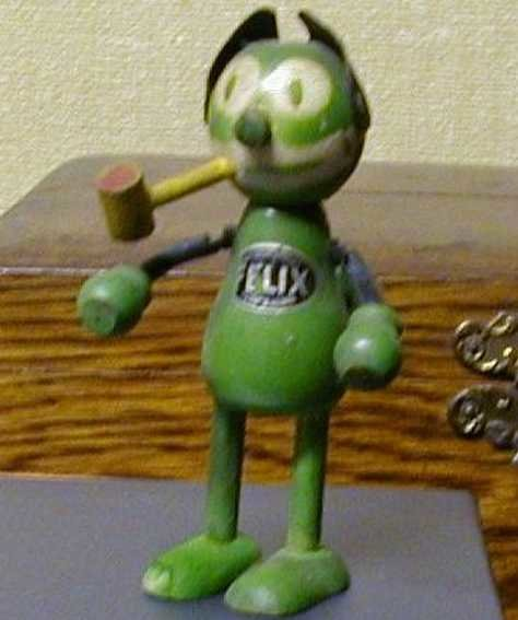 Schoenhut Wood-Figures Felix the cat. He is green and has the little yellow pipe in