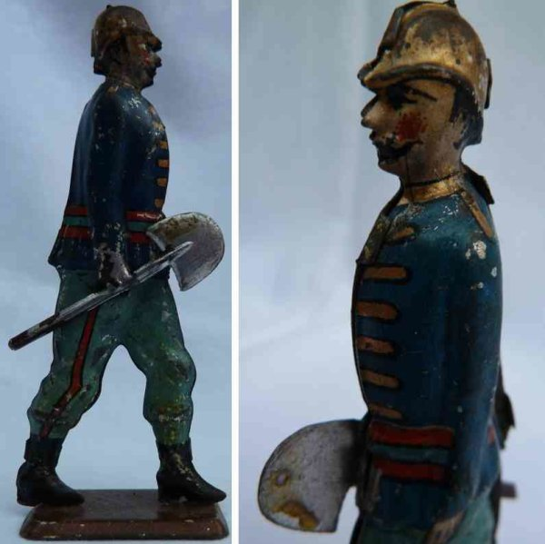 Faivre Jules Edmond Tin-Penny Toy French fireman with shovel (trademark FV, founded in 1864 in