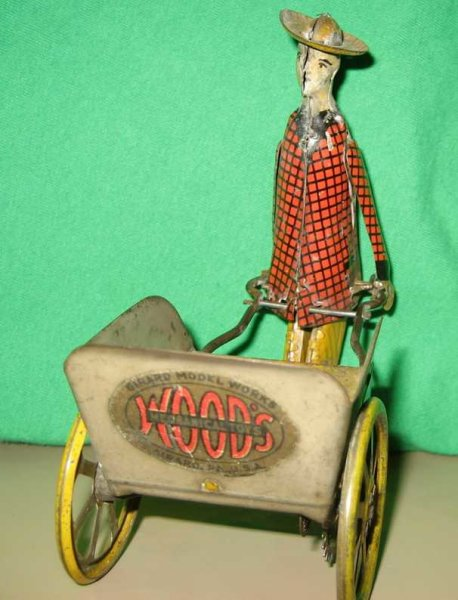 Girard Tin-Figures Porter in red checked jacket pushing a three sided cart with