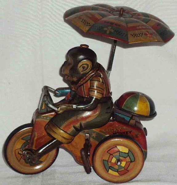 Sato toys Tin-Figures Monkey on cycle lithographed with wind-up mechanism, makers