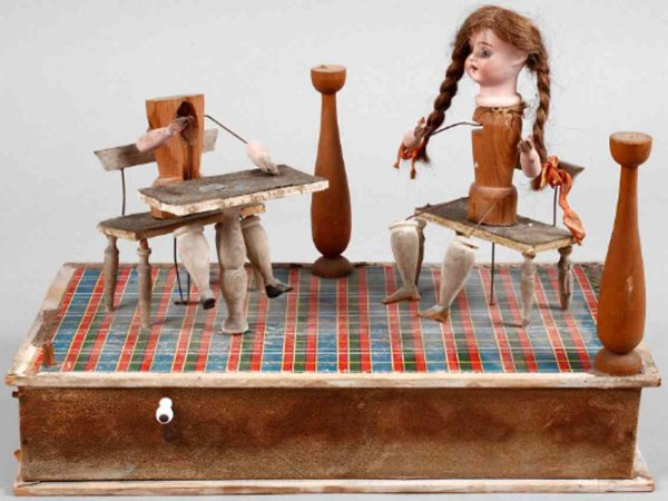 Schönau & Hoffmeister Tin-Automata Doll automat, paper-covered wooden box with two dolls sittin